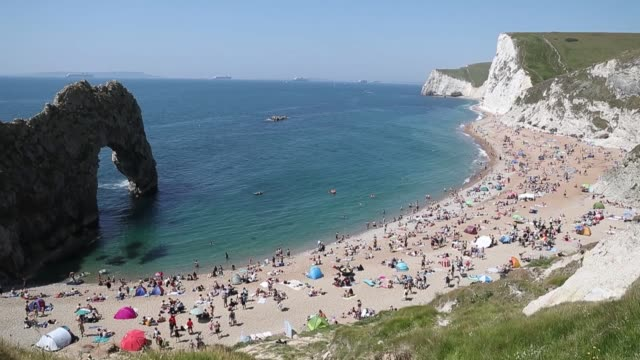 footage of people flocking to durdle door in dorset following the announcement of further easing to lockdown measures - natural arch stock videos & royalty-free footage