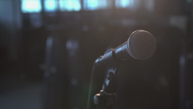 4k footage of planning microphone from right to left over the spot light in music room background - conference event stock videos & royalty-free footage