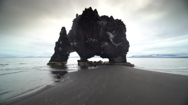 vidéos et rushes de 4k footage of popular hvitserkur dinosaur rock with bird flying in north of iceland - roche sédimentaire