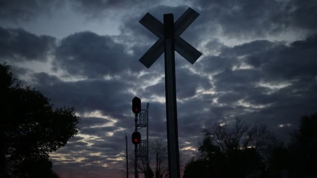 Footage of railroad crossing sign silhouetted against cloudy sky as sun sets in Worthville Kentucky US on Monday April 17 2017