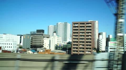 vídeos y material grabado en eventos de stock de imágenes de 4k de escena de la ventana del tren japonés (shinkansen) que ejecutan en tokio, concepto de transporte - vehículo terrestre