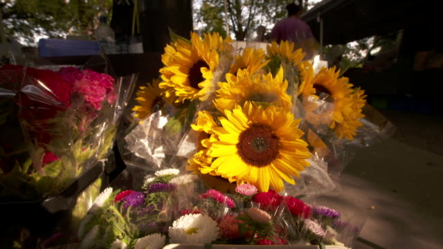 Footage of sunflowers and other types of flowers on displays at the farmer's market
