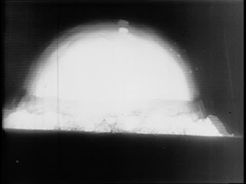 footage of the first atomic bomb blast on desert testing ground / large explosion. - 爆発物点の映像素材/bロール