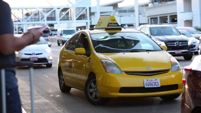 vidéos et rushes de footage of the ride service pick up area at los angeles international airport in los angeles, california, u.s., on monday, november 13, 2017.... - yellow taxi