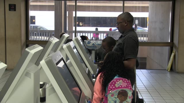 Footage of Travelers at DFW airport checking in at American Airlines and waiting in line for TSA screening in Terminal A