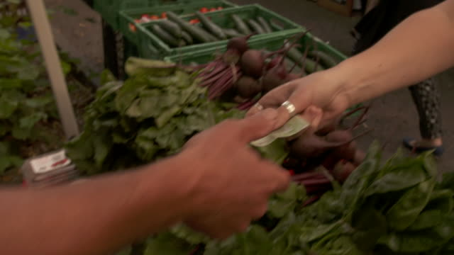 Footage of Vegetables being weighed on scales and paid for with exchange of cash at farmer's market
