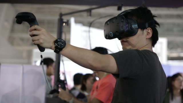 stockvideo's en b-roll-footage met footage of vr gaming and tech at tokyo game show in tokyo, japan on september 16 shots: shot of two people playing bicycle game with vr headsets at... - television game show