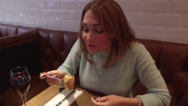 Footage of women placing fork into condiment and taking bite off of the Glamburger in London UK on October 13 2014