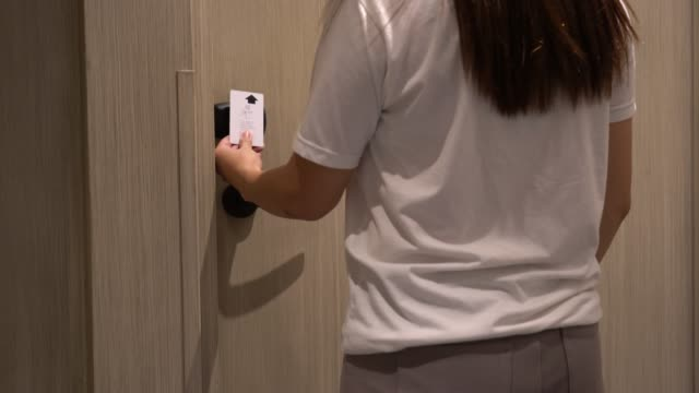 4k footage of young woman using an electronic security key card for opens the door of her hotel room, holiday and leisure concept - accessibility stock videos & royalty-free footage