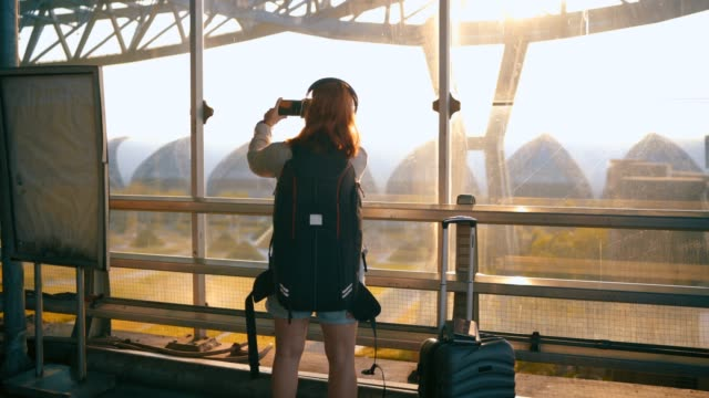 vídeos de stock e filmes b-roll de 4k footage passengers wait for the flight to fly by taking pictures of the sunset. outside the airport - fotografo