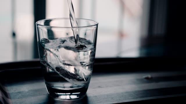 4 k の映像は、澄んだ水のガラスに水を注ぎます。 - カップ点の映像素材/bロール