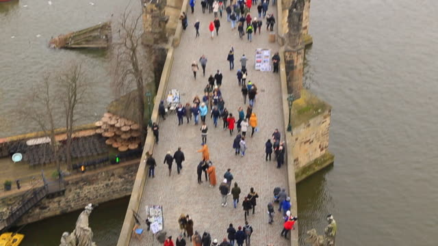 Footage recorded from above in the Charles Bridge of Prague with cityscape and crowd of tourist people walking visiting the city in winter with cloudy day.