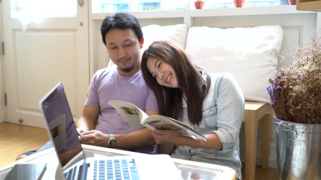 Footage scene of asian woman in casual suit reading and sitting with man using smartphone full of sweet moment in modern co-working space, couple and lifestyle concept