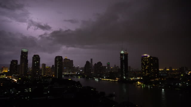 4K Footage scene of lightning with thunderstorm clouds at night over the bangkok cityscape river side, Thailand, nature and cityscape concept