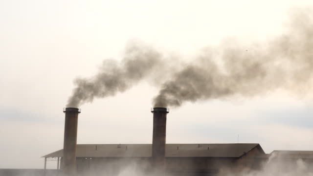 4K Footage scene of Smokestack Factory at the countryside at evening time, zoom in effect, industry and pollution concept