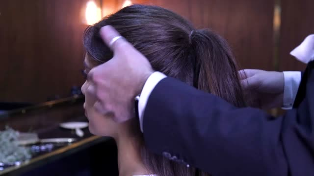 footage shows you how to create a bubble ponytail an easy up do hair look for the christmas party season - coda di cavallo video stock e b–roll