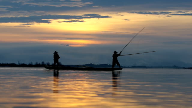 hd footage silhouette of two unidentified traditional fishermen prepare to fishing on the boat - fisherman stock videos & royalty-free footage