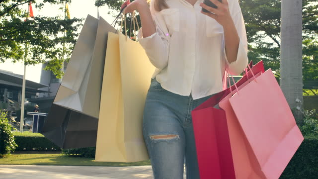 4k footage slow motion the beautiful woman walked outside the mall she is using a mobile phone and carrying shopping bags is colourful and she happily. that has bought things she likes - shopping bag stock videos & royalty-free footage