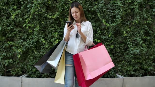 vidéos et rushes de 4k footage slow motion la belle femme marchait à l'extérieur du centre commercial elle utilise un téléphone mobile et portant des sacs à provisions est coloré et elle heureusement. cela a acheté des choses qu'elle aime - sac