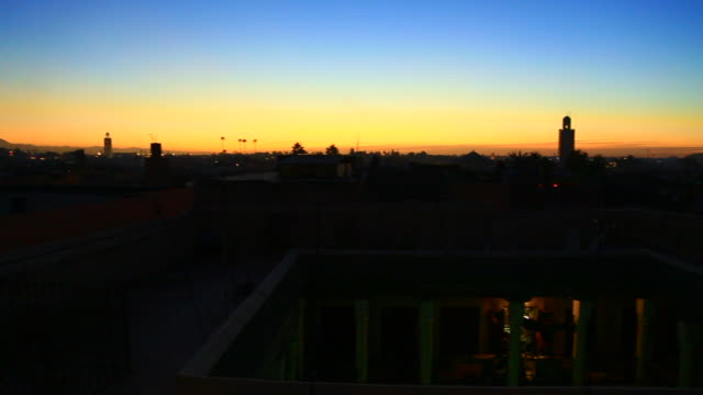 footage takem from elevated viewpoint in buiding terrace contemplating the skyline of marrakech at almost night with sunset colors in the sky and the mosque silhouettes with the sky during travel vacations in morocco. - moroccan culture stock videos & royalty-free footage
