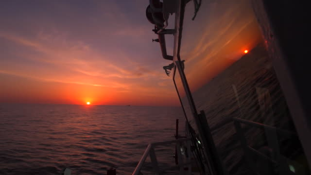 footage taken from a ship of the sun setting on the horizon while on the open ocean - animal eye stock videos & royalty-free footage