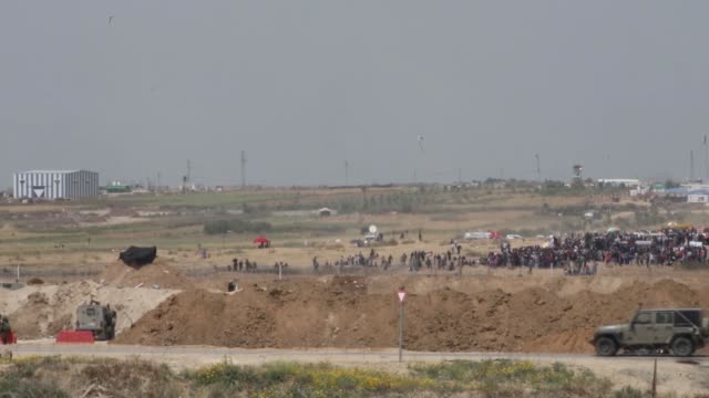 footage taken in nahal oz region of israel on april 13, 2018 shows thousands of palestinians converged along the gaza strip's eastern border with... - 70周年点の映像素材/bロール