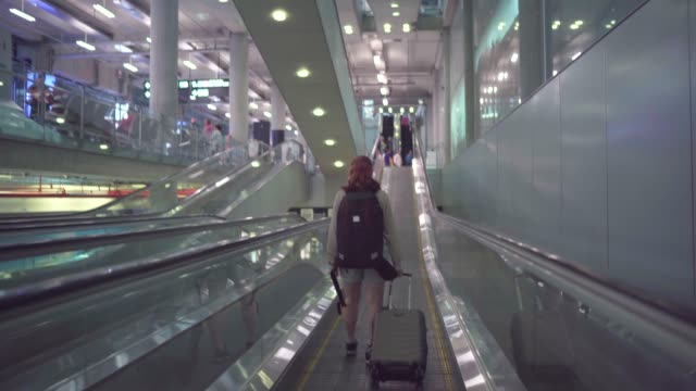 4k footage travelers drag the luggage, walk towards the escalator in the airport - elevated walkway stock videos & royalty-free footage