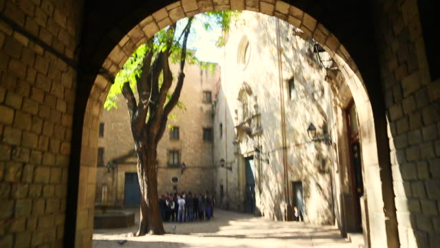 footage walking from personal perspective in the barcelona gothic quarter entering in a nice hidden square with church and sunny day. - gothic quarter barcelona stock videos and b-roll footage