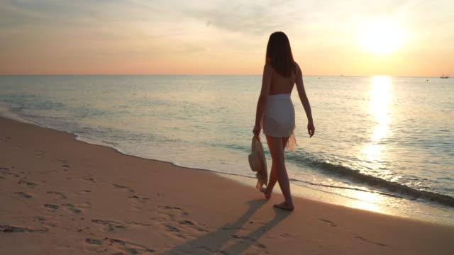 vidéos et rushes de images 4k les femmes sont joyeuses. elle marche seule sur la plage et joue dans la mer. - belle femme
