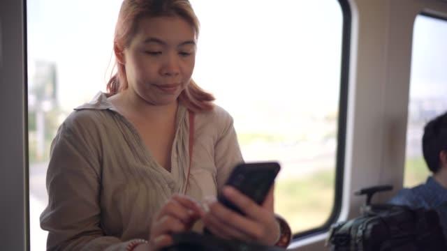 4K Footage Women spielen Handys und hören Musik Während warten, bis der Zug zum Flughafen zu gehen.