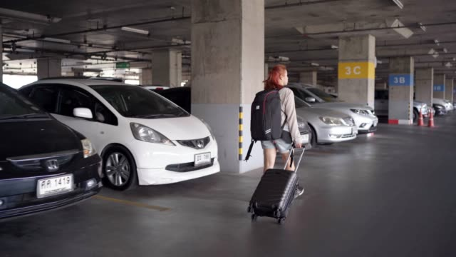 4k 映像女性旅行者は屋内駐車場で車からバッグを取り出します。 - 駐車点の映像素材/bロール