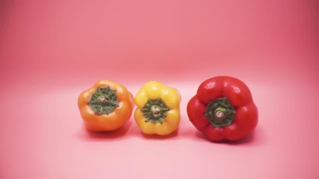 vídeos de stock e filmes b-roll de 4k footage zoom effect colourful sweet pepper in pink background. - ingrediente