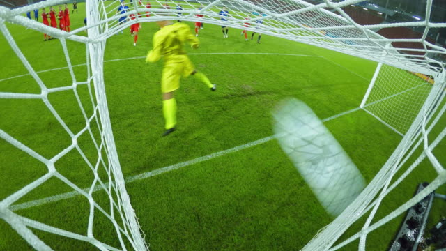 ld football ball striking the net at a game - tor konstruktion stock-videos und b-roll-filmmaterial