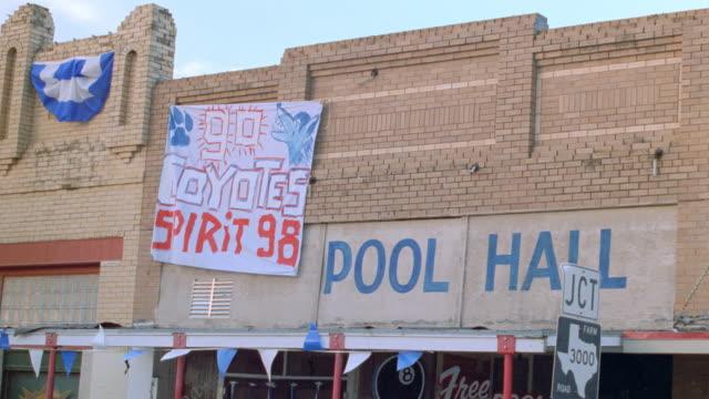vídeos y material grabado en eventos de stock de a football banner hangs above a pool hall storefront. - salón de billares