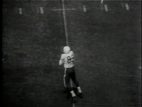 vídeos y material grabado en eventos de stock de football being passed then player being knocked out of bounds / united states - 1958