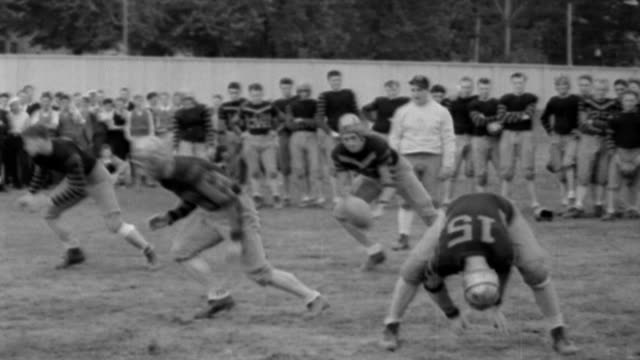 football coach frank carideo talks to camera / football teams runs onto pitch / men running and catching balls during practice / practicing tackles... - 1932 stock-videos und b-roll-filmmaterial