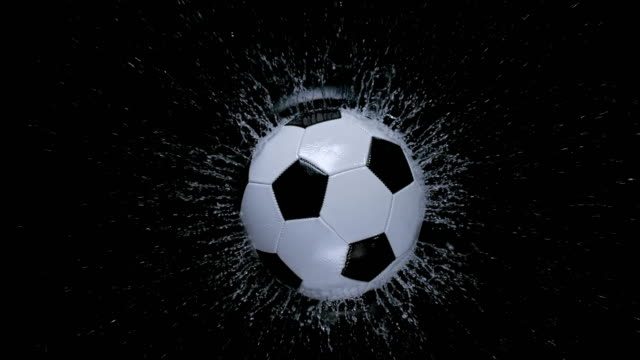 vídeos de stock e filmes b-roll de slo mo ld football falling into water on black background - ball