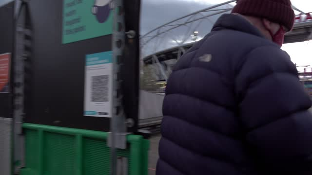 football fan uses a covid track and trace app on his phone to enter the west ham united stadium on december 05, 2020 in london, england. it is the... - 接触者追跡点の映像素材/bロール