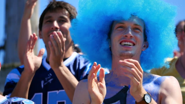 MS Football fan wearing wig and body paint standing and cheering with crowd during game