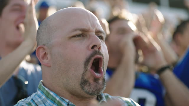 SLO MO. Football fans cheer and high five in crowded stadium.