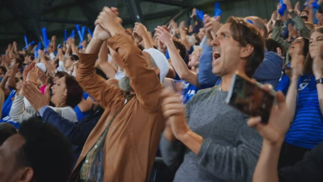 stockvideo's en b-roll-footage met football fans cheering on the stadium tribune and a woman making a smartphone video - toeschouwer