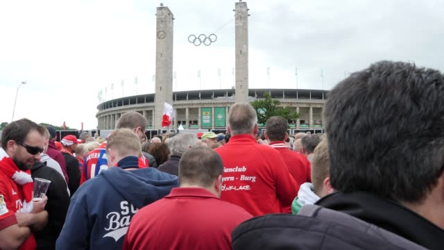 Football fans from FC Bayern Munich in front of the stadium with the Olympic rings in the background ahead of the DFB Cup Final 2019 between RB...