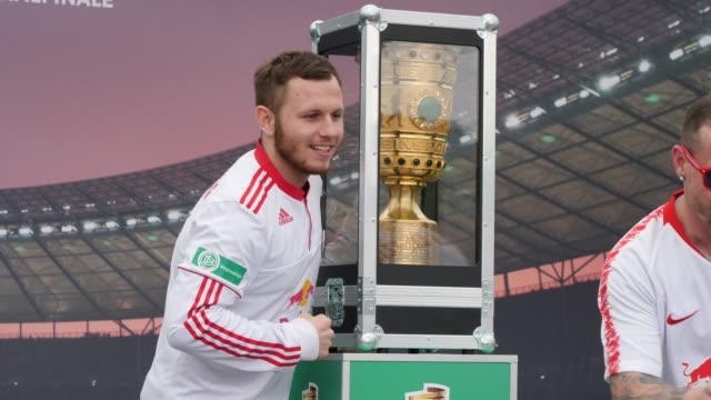 Football fans from RB Leipzig pose with the real DFB Cup which is displayed in front of the stadium ahead of the DFB Cup Final 2019 between RB...