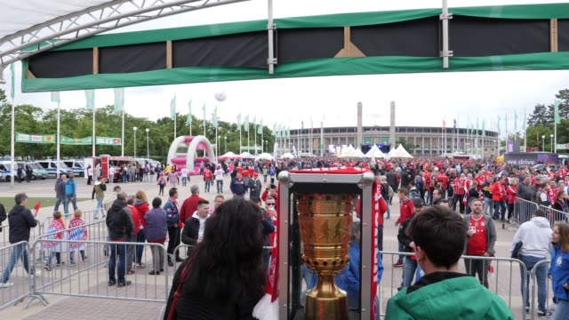 Football fans pose with the real DFB Cup which is displayed in front of the stadium ahead of the DFB Cup Final 2019 between RB Leipzig and Bayern...