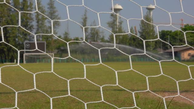 灌漑の背景を持つサッカーの目標ネット - カーテン レース点の映像素材/bロール