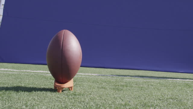 A football is kicked off a tee