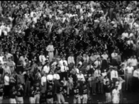 vidéos et rushes de football on tee on field line laced athletic shoes kicking football ws tu stands filled w/ cheering people fans ha ms game play #47 running w/... - 1952