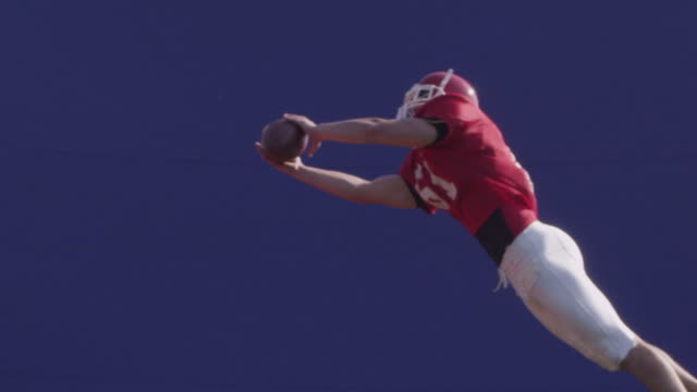 A football player catches a football with blue screen, slow motion