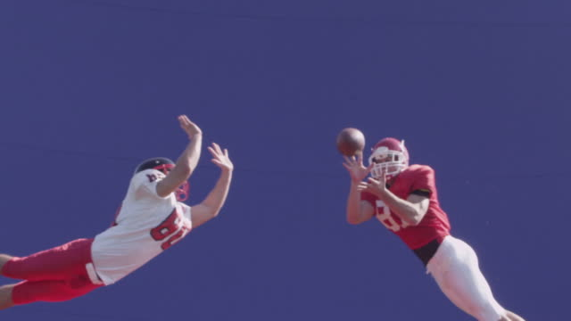 A football player catches a pass in mid-air, slow motion with bluescreen