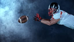 SLO MO LD Football player catching the ball in the air on the field at night